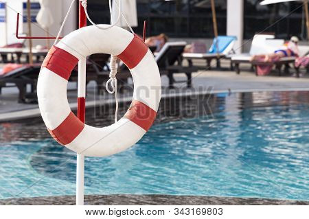 Red Lifebuoy Ring Near The Swimming Pool. Rescue Concept.