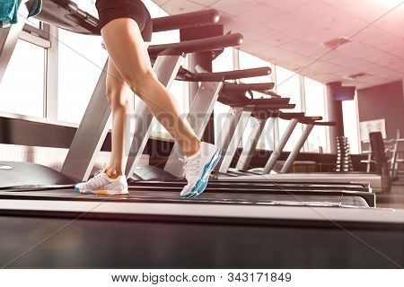 Close Up Womans Legs Running At The Treadmill In The Gym Over Sunrise. Wearing In White Orange Blue