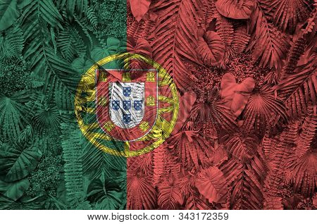 Portugal flag depicted on many leafs of monstera palm trees. Trendy fashionable backdrop poster