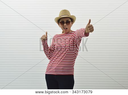 Cheerful Young Asian Woman Wearing Red Stripped Shirt, Sunglasses, Straw Hat And Jeans Making Thumbs