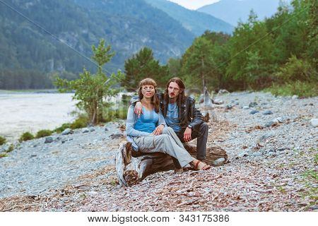 A Couple Of Lovers Sit Near The River And Look At The Landscape