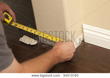 Contractor Measuring for New Baseboard with Bull Nose Corners and New Laminate Flooring Abstract.