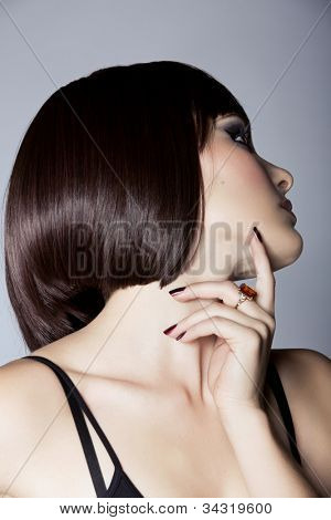 portrait of a beautiful woman in short brunette bob with neat clean hair on studio background - focus on the eye and the face skin.