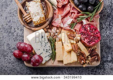 Traditional Italian Antipasto Plate. Assorted Cheeses On Wooden Cutting Board. Brie Cheese, Cheddar