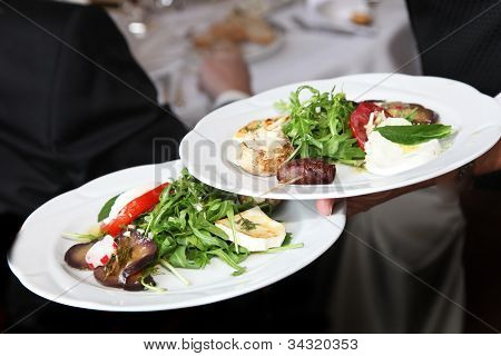Waiter Carrying Plates Of Starters