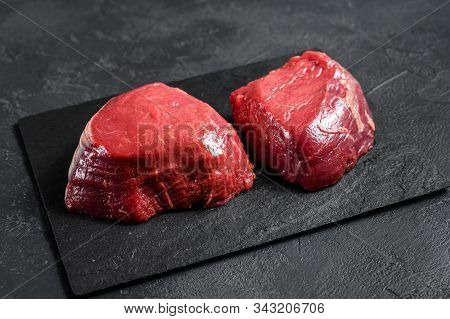Raw Steaks Fillet Mignon Prepared For Cooking. Beef Tenderloin. Black Background. Top View