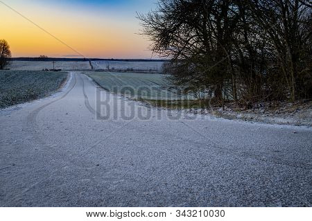 Snow Covered Road With Tracks In A Rural Winter Landscape At Sunset With Orange Glow On The Horizon