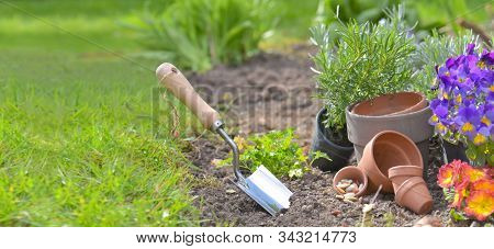 Shovel Planted In The Soil Of A Garden Next To Teracotta Pots And Flowers With Copy Space In Grass B