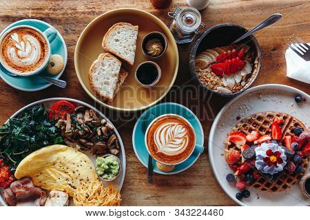 Morning Breakfast On A Table Above, Waffles With Cream, Berries, Coffee, Cappuccino, Bowl, Omlet Wit