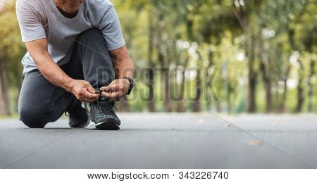 Asian Senior Man Tying Running Shoes At The Park. Banner, Panoramic.