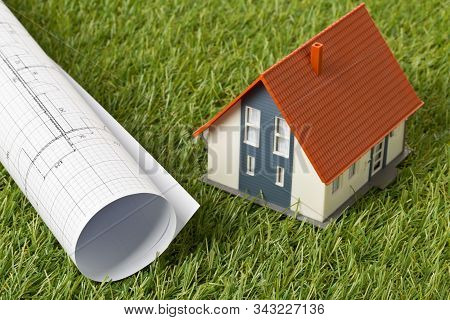 Miniature House Model With Architectural Blueprint On Green Grass Lawn Background - House Building O