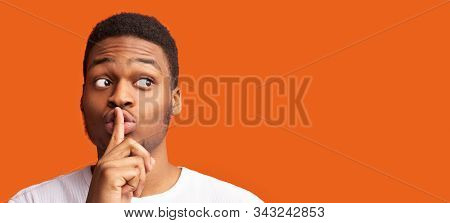 Shh, Its A Secret. Black Man Making Silence Gesture Putting Finger On His Lips Looking At Copy Space