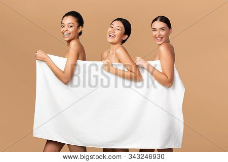 Beauty And Body Care. Three Multiracial Girls Holding White Bath Towel Smiling At Camera Posing Over