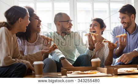 Overjoyed Multiethnic Millennial Friends Eating Pizza At Home