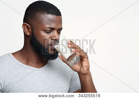 Thirsty Young African Man Holding Glass Of Drinking Water For Body Health, Healthy Lifestyle, Thirst