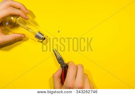 Pliers And Splinters From The Glass Light Bulb Isolated On Yellow Background