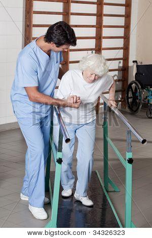A doctor assisting a senior citizen .
