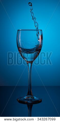 Beautiful Splash Of Water In A Glass On A Gradient Blue Background