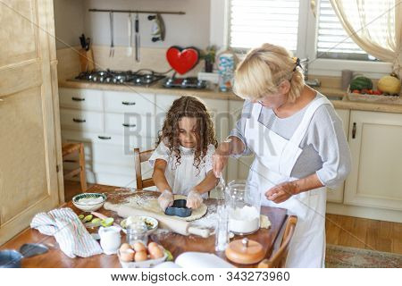 Adorable Curly Little Girl With Her Grandmother Cooking Together At Kitchen Table. Helps Grandma In