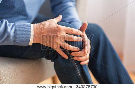 Unrecognizable Senior Man Massaging His Knee Suffering From Arthritis Pain Sitting On Sofa Indoor. C