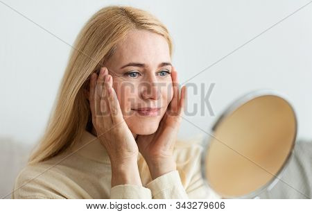 Perfect Skin. Middle-aged Woman Satisfied With Her Skin, Looking At Round Mirror