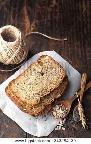 Slices Of Homemade Dark Fragrant Fresh Bread With Poppy Seeds, Flax, Sunflower And Pumpkin On Dark W