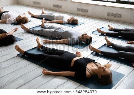 Young People Meditating In Savasana Pose, Practicing Yoga At Lesson