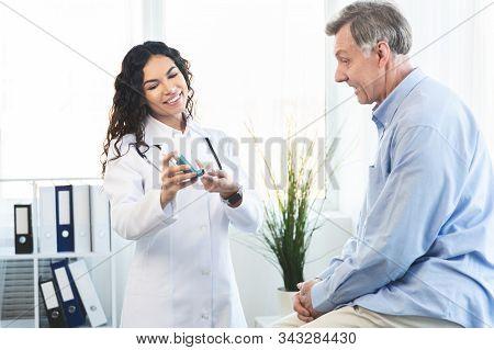 Medicine Concept. Brazilian Doctor Giving Asthma Inhaler To Elderly Man Whos Sitting On Examination