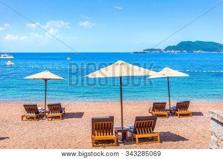 Sandy Beach In Sveti Stefan With Chaise-longues And Umbrellas At Summer Day, Montenegro