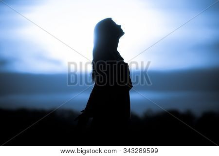 Youth Woman Soul At Red Sun Meditation Dreaming Past Times. Silhouette In Front Of Sunset Or Sunrise