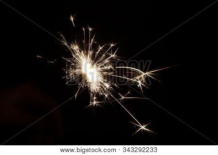 Sparkler With Light And Fire In Hand Of Child During New Years Eve