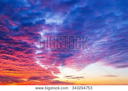 Sunset Fire In The Sky. Dark Blue Clouds With Red Reflections Of The Setting Sun. Scenic Sundown Clo