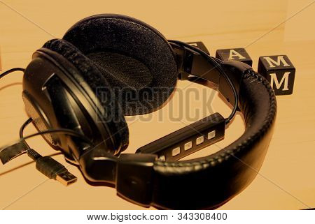 Modern Headphones With Cables On Wooden Table