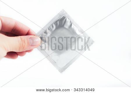 Female Hand Holds A Silver Condom In A Package On A White Background