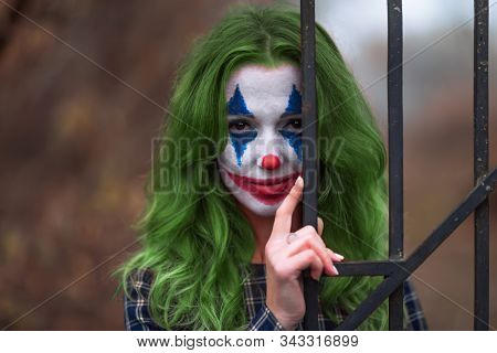 Close-up Portrait Of A Greenhaired Girl In Chekered Dress With Joker Makeup On A Blurry Background.