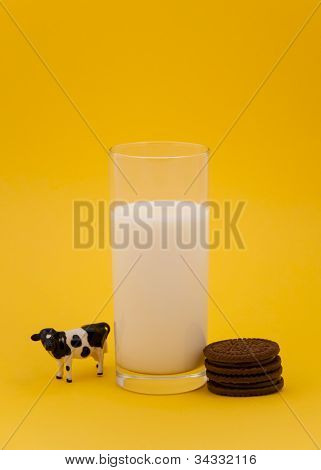 Toy cow and cookies with glass of milk isolated on yellow background
