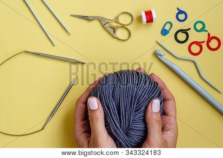 Knitting Tools On A Yellow Background. Skein Of Thread, Pins, Markers, Row Counter, Knitting Needles
