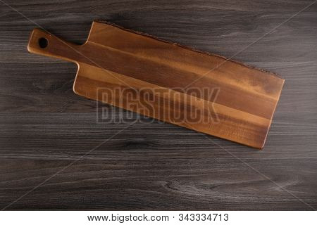 Top View Of Wooden Cutting Board On Old Dark Wood Countertop.