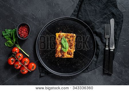 Piece Of Tasty Hot Lasagna. Traditional Italian Food. Black Background. Top View
