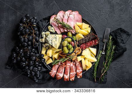 Antipasto Board With Sliced Meat, Ham, Salami, Cheese, Olives. Black Background. Top View