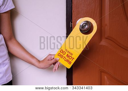 Woman Hands Putting Closed Door With Please Do Not Disturb Sign On Handle At Hotel Room