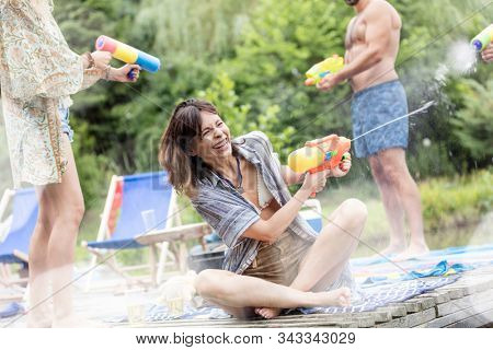 Cheerful couples enjoying with squirt guns on pier during summer