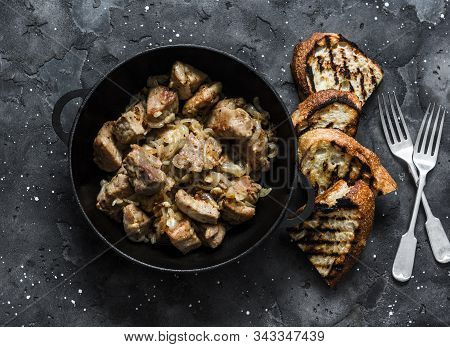 Roast Pork With Onion, Garlic And Hot Pepper In A Cast Iron Pan On A Dark Background, Top View