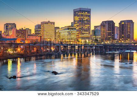 Richmond, Virginia, USA downtown skyline on the James River at twilight.