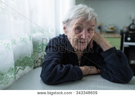 Lonely old woman sitting in the kitchen by the window in his house.