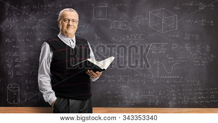 Elderly male teacher holding a book and standing in front of a blackboard with math formulas