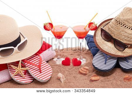 Beach accessories, seashells, sand, two glasses with cocktail and red hearts on white background.  Vacation  in warm countries, beach holiday and party. Honeymoon. Valentine's Day. Romantic travel