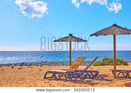 Beach with parasols and chaise longues by the sea at seaside resort on sunny summer day