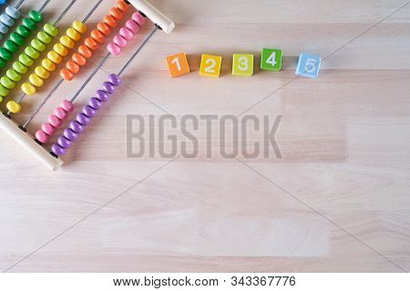 Flat Lay, Top View Of Bright Colored Wooden Bricks And Abacus Toy Background With Copy Space For Tex