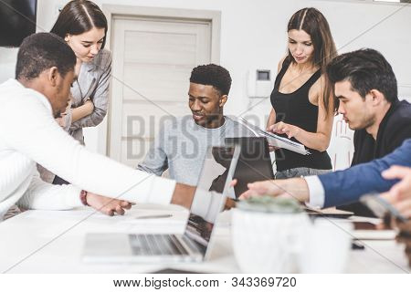 A Team Of Young Office Workers, Businessmen With Laptop Working At The Table, Communicating Together